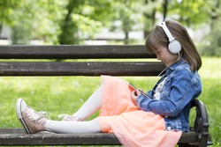 Little girl in a skirt sitting on a park bench, listening to music and looking at mobile phone