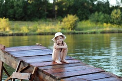 Little girl in a straw hat and swimsuit at a river lake shore on sunset sitteing on wooden pier. Relaxing in nature