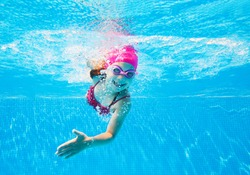 little girl in a striped bathing suit swims in the pool underwater