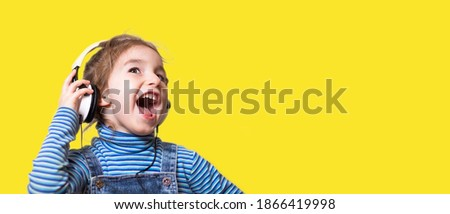 Little girl in a striped blue turtleneck listens to music with white headphones and sings loudly with her mouth open. Fun, shouting, children's emotions. Yellow background, banner, copy space Stock fotó ©