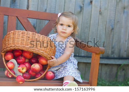 Little girl in a summer dress sits on a wooden shop with apples