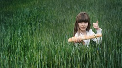 Little girl in a wheat field with a baguette in his hands. Shows like exquisite and delicious loaf. The concept of the origin of bread.