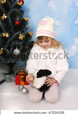 little girl in a white coat and hat with a rabbit around a Christmas tree