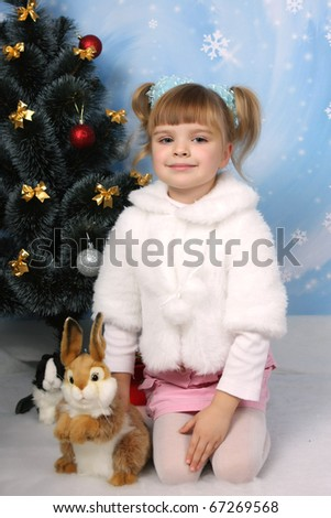 little girl in a white coat with a rabbit around a Christmas tree
