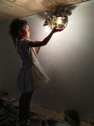 little girl in a white dress held out her hands to the light