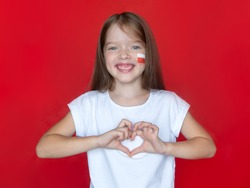 Little girl in a white T-shirt with a Polish flag on her cheek shows a heart gesture with her hands, concept for learning Polish, immigration to Poland