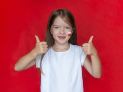 Little girl in a white T-shirt with the Polish flag on her cheek shows thumb up gesture, concept of learning the Polish language, immigration to Poland
