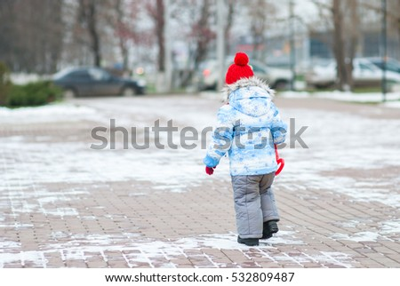 Little girl in a winter suit and a red cap is on the square. We see the back.