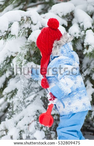Little girl in a winter suit and a red shovel snow from paw shakes trees