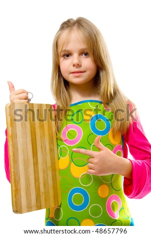 Little girl in apron pointing at cutting board