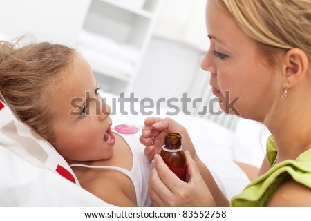 Little girl in bed taking medicine with plastic spoon