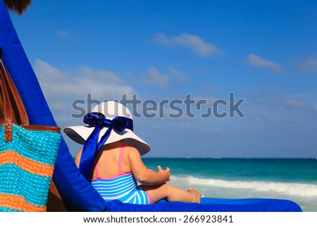 little girl in big hat on summer tropical beach #266923841