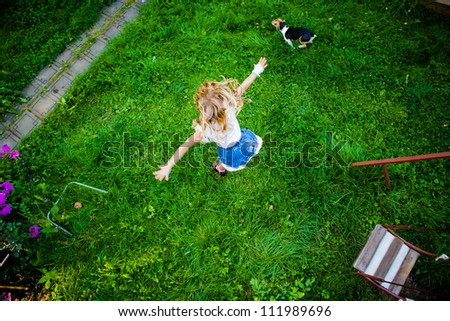 Little girl in blue dress jumping from the swing and the running dog with a slight motion blur and sharp grass background