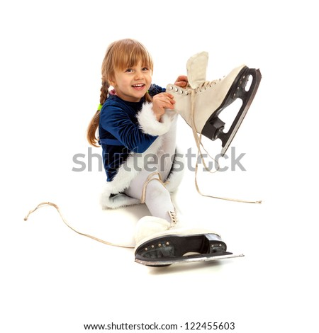 Little girl in blue dress smiling and putting on big skates isolated on white