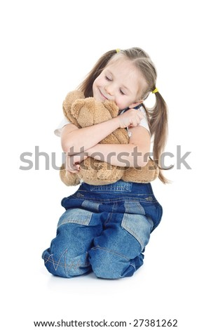 little girl in blue jeans seats hugging with toy bear