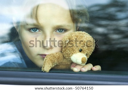 Little girl in car is going to miss her friends.