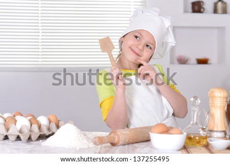 little girl in chef hat and apron  preparing  in the kitchen