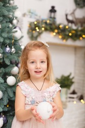 Little girl in Christmas decorated room near fit-tree. Christmas celebration. New year eve. Garland lights on a background. Child Girl weared in pink dress holding a New Year ball in her hands