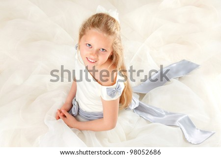 little girl in communion smiling and looking up - stock photo