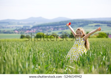 Stock Photo Little girl in cornfield with wide open arms. Child relaxing and rejoicing in front of village landscape