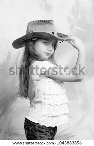 little girl in cowboy or cowgirl outfit with raised hand to hat on colorful background #1043883856