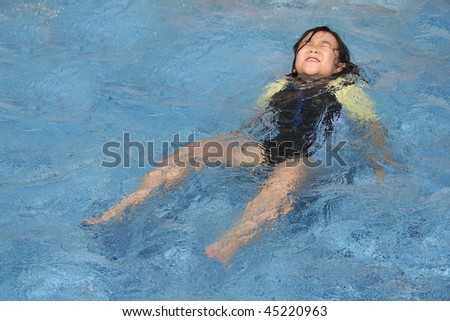 Little girl in danger drowning in the swimming pool - stock photo