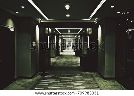 Little girl in dark corridors and light in the building. Black and white. #709983331
