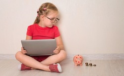 Little girl in eyeglasses using notebook laptop sitting on the floor at home with piggybank and coins money. Education homeschooling finance and savings concept.