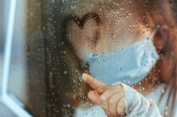 Little girl in face mask drawing heart symbol on the window glass with rain drops. Selective focus on the heart. Social isolation stay at home during Pandemic COVID-19 concept.