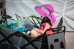 Little girl in fold-up wagon at outdoor market with plants and bags and bright pink sun hat hiding face