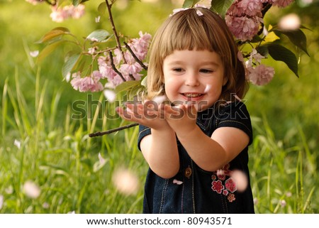 Little girl in garden, under the sakura tree. Spring petal's rain.