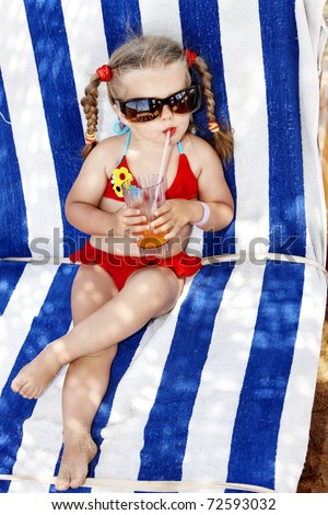 Little girl in glasses and red bikini drink orange juice.