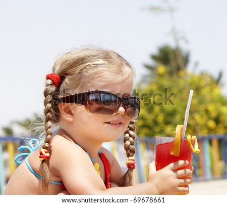 Little girl in glasses and red bikini on playground drink  juice.