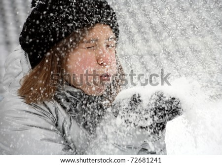 little girl in gloves and hat blowing snow on park