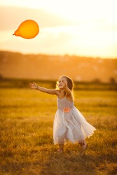 little girl in grey dress runs for with a balloon on a sloping a wheat field in the village at sunset