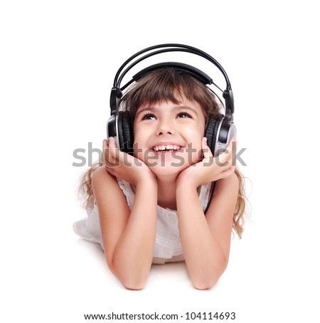 Little girl in headphones listening to the music and looking to the copy space area
