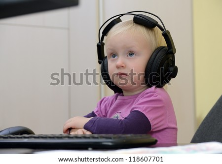 little girl in headphones on the computer learning - stock photo