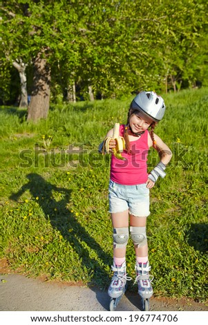 Little girl in helmet and roller skates at a park. children outdoors. sports food
