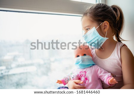 Little girl in hospital. Child girl with doll wearing a protective mask. Copy space. Sadness kid at home in isolation. Sick child   Little girls look at the window with longing