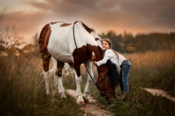 Little girl in indian style with pinto pony in a summer field in sunny evening