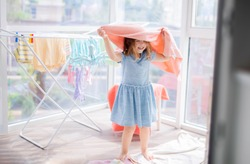 Little girl in laundry room. Clean washed clothes on drying rack. Mother's little helper, little girl helping with laundry, she hangs up towels for drying