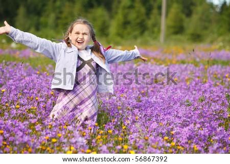 Little girl in meadow full of summer flowers