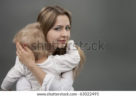 Little girl in mother's arms seeking protection and comfort