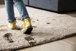 Little girl in muddy shoes messing up carpet at home