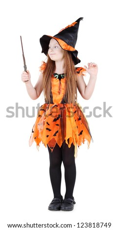 Little girl in orange costume of witch for Halloween holds and looks at wand isolated on white background.