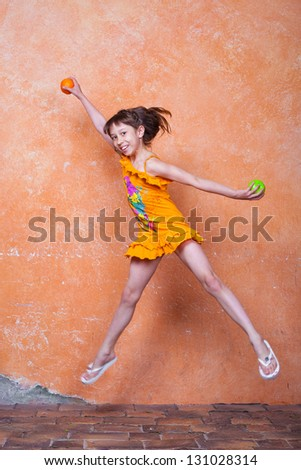 little girl in orange dress jumping beside the orange wall with orange and apple in her hands