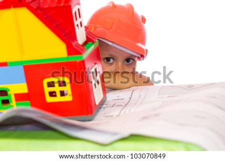 Little girl in orange helmet looking from behind the house