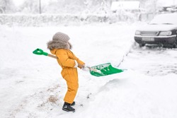 Little Girl in orange jumpsuit cleans snow big shovel. Snow removal after heavy snowfall. a child with difficulty lifts a shovel with snow from a snowdrift.