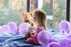 little girl in pajamas sitting on a blue blanket on the balcony with teddy bear and holding a cup, lying on the floor balloons