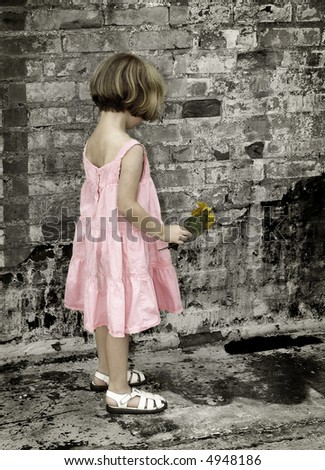 Little girl in pink dress with brick background in colorized black and white